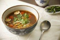 Dulce y amarga sopa de verduras con pollo en tazón de fuente sobre la mesa con la cuchara - foto de stock