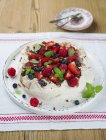 Closeup view of Pavlova with berries and mint leaves on platter — Stock Photo