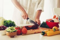 Woman chopping vegetables in a kitchen with knife in hand over chopping board — Stock Photo