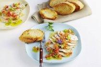 Putenbrust mit Kräutern und einer Tomaten-Vinaigrette auf blauen Teller mit Gabel auf weißem Untergrund — Stockfoto