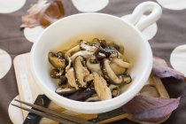 Mushroom umatsukuda-ni Simmered dish in soy sauce and sugar on white plate over wooden desk — Stock Photo