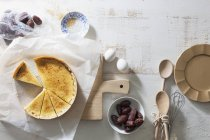 Crme brle tart and dates over wooden surface with wooden desk and paper — Stock Photo
