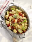 Vegetarian summer gnocchi with courgettes in metal dish over wooden white surface — Stock Photo
