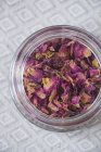 Вид сверху на сушеные лепестки роз в стеклянной банке — стоковое фото