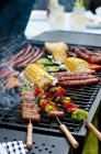 Sausage kebabs, sausages and vegetables on a barbecue rack outdoors — Stock Photo