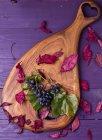 Uvas y hojas otoñales sobre una tabla de madera - foto de stock