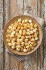 Palomitas de maíz en placa de madera - foto de stock
