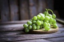 Green grapes on a rustic wooden table — Stock Photo