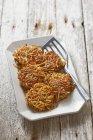 Buñuelos de verdura de raíz con tomillo y mostaza de placa blanca con servidor sobre superficie de madera - foto de stock