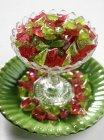 Крупним планом подання з червоними та зеленими солодощі в скляну миску — стокове фото