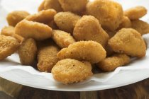 Montón de nuggets de pollo en la placa - foto de stock