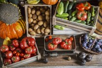 Crates of fresh fruit and vegetables over wooden surface — Stock Photo