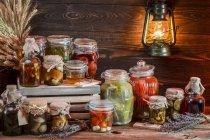 Різні банки консервовані гриби і овочів з дерев'яними тлі — стокове фото