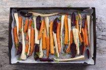 Légumes racines rôtis et betterave rouge sur une plaque de cuisson — Photo de stock