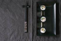 Maki sushi on black plate — Stock Photo