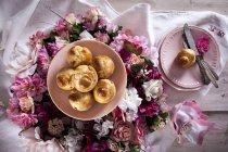 Vista superior de Brioches en plato y corona de flores de colores - foto de stock
