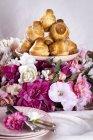 Крупный план кучи бриошей на тарелке и цветах — стоковое фото