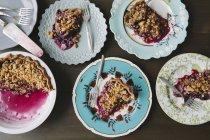 Vista superior de las porciones de tarta de arándano sobre placas con horquillas - foto de stock