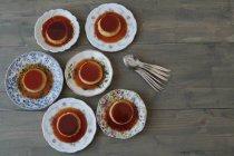 Vue de dessus de six assiettes Creme caramel en sauce sucrée sur la surface en bois — Photo de stock