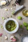 Vista superiore del Pesto in un mortaio con foglie, aglio, olio e pane intorno — Foto stock