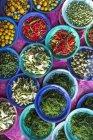 Fiori commestibili, melanzane, alghe di fiume e peperoncini in un mercato — Foto stock