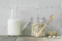 Avena in barattolo e bottiglia di latte — Foto stock