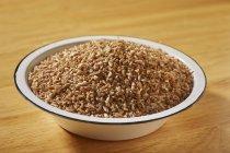 Raw bulgur in enamel bowl — Stock Photo