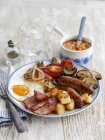 A classic English breakfast on white plate over wooden surface with fork — Stock Photo