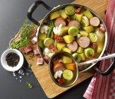 Овощное рагу с колбасы и сала на сковороде на деревянный стол — стоковое фото