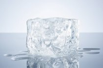 Closeup view of a block of ice on a reflective surface — Stock Photo