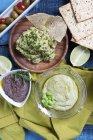 Три погружения: гуакамоле, оливковая паста и гороховый крем в мисках за столом — стоковое фото