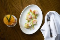 Pickled rhubarb, basil foam and radish on scallop slices on white plate  over wooden surface — Stock Photo