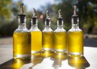 Крупный план масла в бутылках с наливками на открытом столе — стоковое фото
