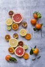 Top view of different types of sliced exotic fruits with whole oranges and leaves — Stock Photo