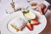 Primo piano ritagliata vista della mano che tiene la piastra con strudel di mele con vaniglia e fragole — Foto stock