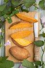 Patata dolce affettata con foglie e fiori — Foto stock