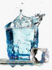 Ice cube falling in a glass of water — Stock Photo