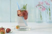 Vista de primer plano del agua aromatizada con fresas y menta en un vaso con una paja - foto de stock