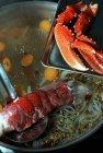 Vista de cerca de las garras de langosta y la cola en skimmer sobre sopa de verduras - foto de stock