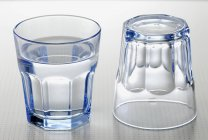 Glass of water and empty glass — Stock Photo