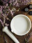 Vista superiore del latte di cocco in un mortaio con un pestello e lavanda fiori — Foto stock