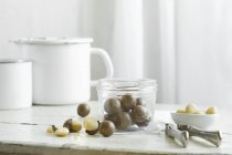 Closeup view of Macadamia nuts in a glass jar and a nutcracker on a rustic kitchen table — Stock Photo