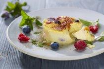Крупним планом вид на крем-брюле з ягід і листя на тарілці — стокове фото
