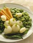 Белая тарелка овощей на текстильной поверхности — стоковое фото