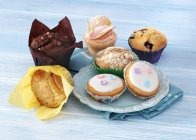 Cupcakes and Muffins on a blue surface — Stock Photo
