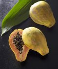 Papayes fraîches entières et coupées en deux — Photo de stock
