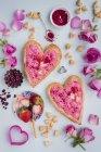 Vista de cerca de las tartas de hojaldre en forma de corazón con crema de rosas, fresas y espolvoreos - foto de stock