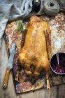 Roast goose with knife — Stock Photo