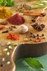 Assorted spices scattered on wooden desk — Stock Photo