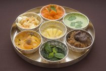 Tray of seven Indian chutneys over brown surface — Stock Photo
